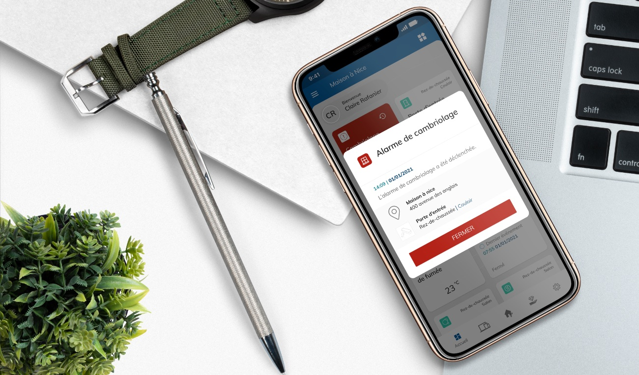 Smartphone sur un bureau affichant une notification de cambriolage