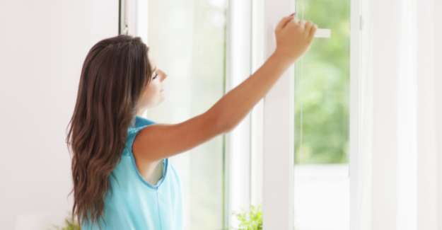 A lady opens the window and enjoy fresh air