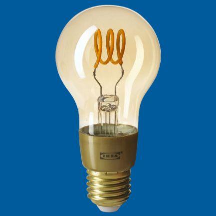 Ikea orange smart light filament bulb on a blue background compatible with Nearsens