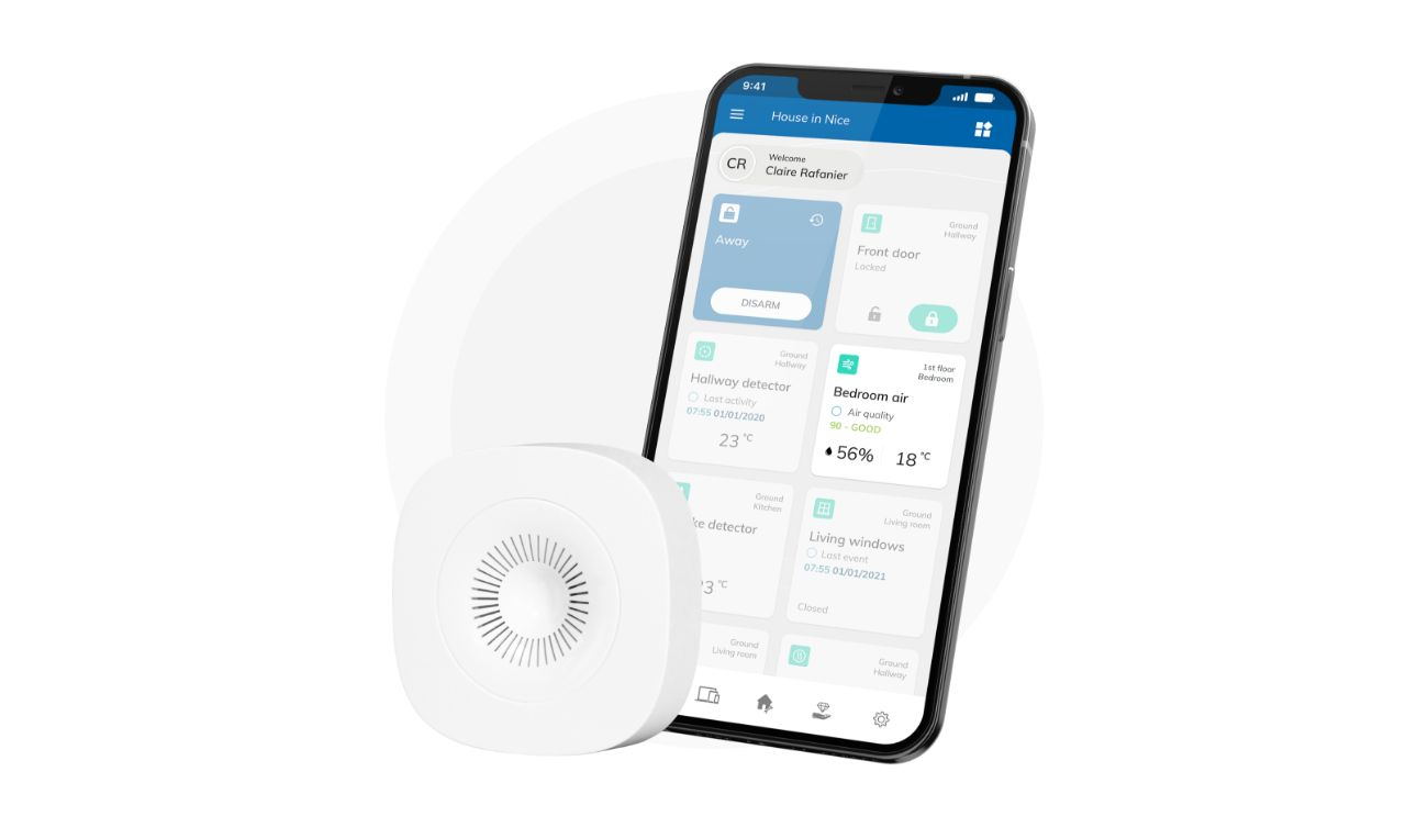 Air quality sensor with a black smartphone focusing on the air quality tile in a room