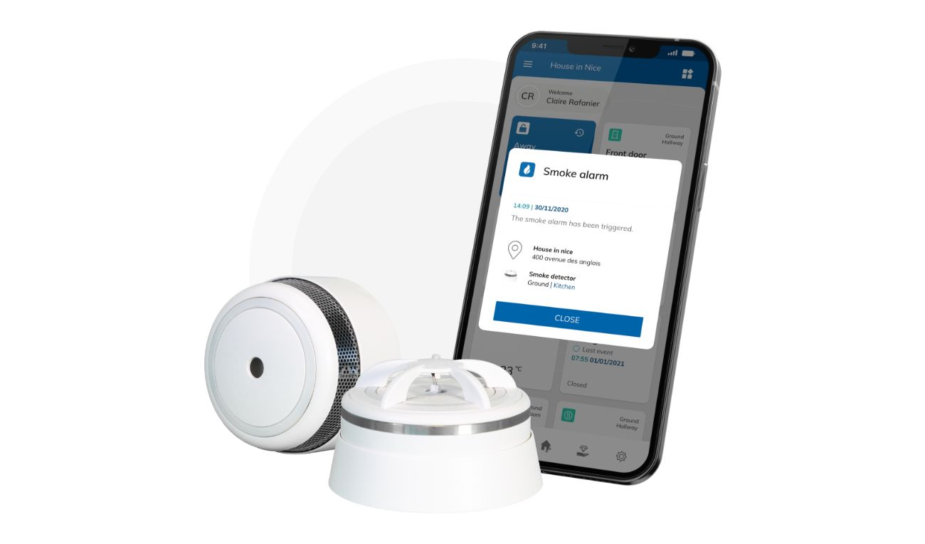 White smoke and heat detector with black smartphone showing smoke alarm notification