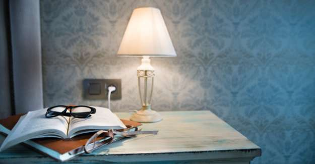 2 diaries and a glass on a table with a lamp