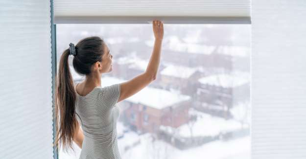 Young lady opens the blinds from her room and sees snow outside