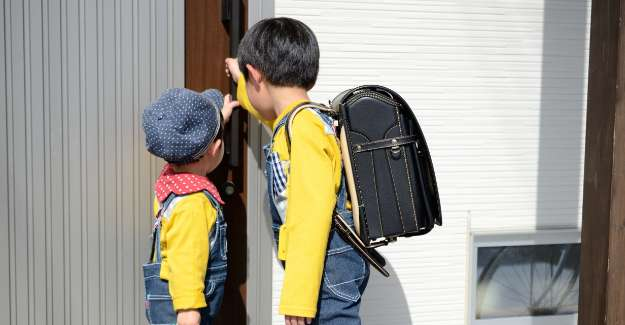 Two little boys comeing back from school and ringing the door