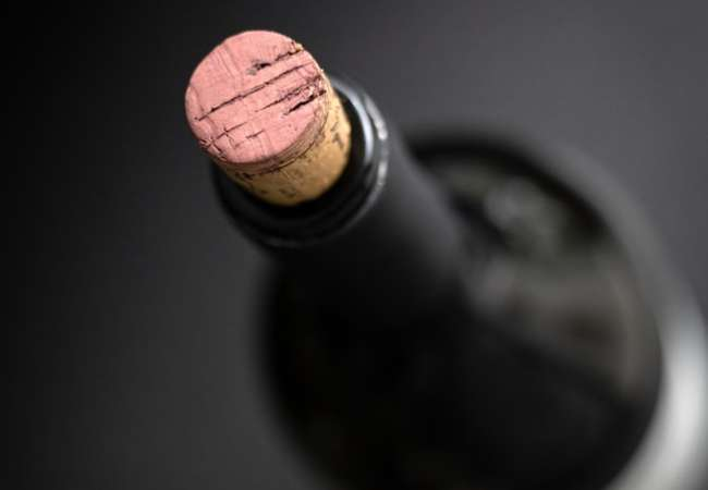 Bottle of red wine with the cap pointing to us