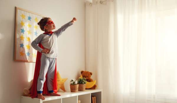 little girl disguised in super woman standing on the table pointing her fist to the sky
